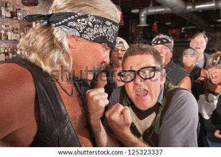 Angry nerd with clenched fists facing strong gang member - stock photo