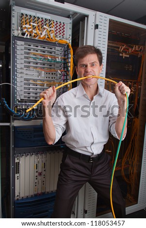 Angry Network engineer in server room bites cable - stock photo