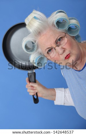 Angry old lady threatening to use frying pan - stock photo