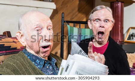 Angry older couple reading newspaper in living-room - stock photo