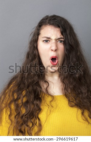 angry overweight 20's woman with long brown hair screaming loud for expressing rage and impatience - stock photo