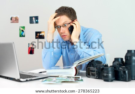 Angry photographer discussing photos with client by mobile phone. - stock photo