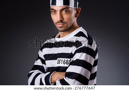 Angry prison inmate in dark room - stock photo