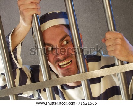 Angry prisoner in a prison. - stock photo