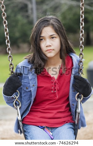 Angry, sad preteen girl sitting on swing - stock photo