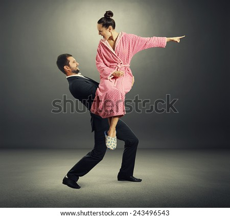 angry screaming woman in dressing gown sitting on the hands her husband over dark background - stock photo