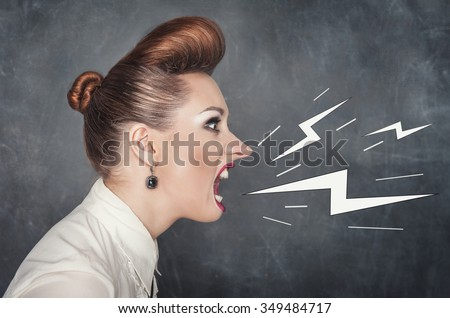 Angry screaming woman on the blackboard background - stock photo