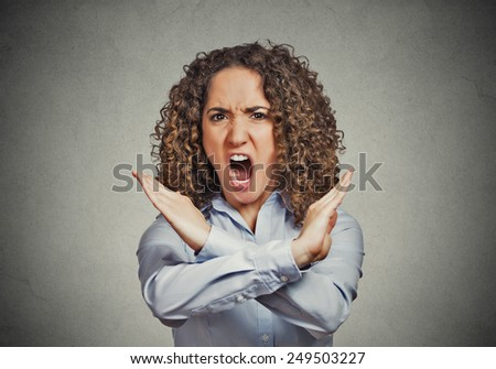 Angry screaming young woman making showing stop gesture isolated on grey wall background Negative human emotion facial expression feelings, sign symbol body language, reaction nonverbal communication  - stock photo