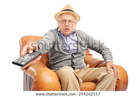 Angry senior man pressing buttons on a remote control seated in an armchair isolated on white background - stock photo