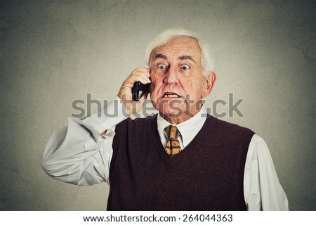 Angry senior man talking on mobile phone isolated on gray wall background. negative emotions  - stock photo