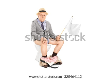 Angry senior man waving a white flag seated on a toilet isolated on white background - stock photo