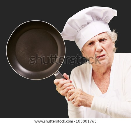 angry senior woman cook trying to hit with a pan over a black background - stock photo