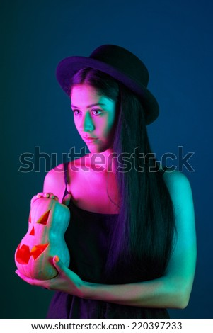 angry sexy young brunette witch. isolated against dark background - stock photo