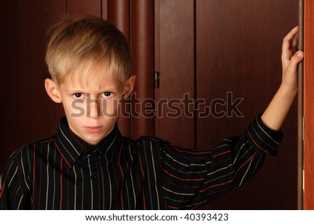 Angry six-year-old boy standing against dark background - stock photo