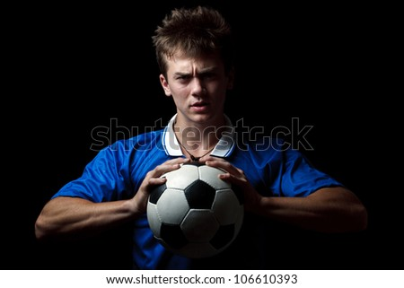 Angry soccer player with a ball - stock photo