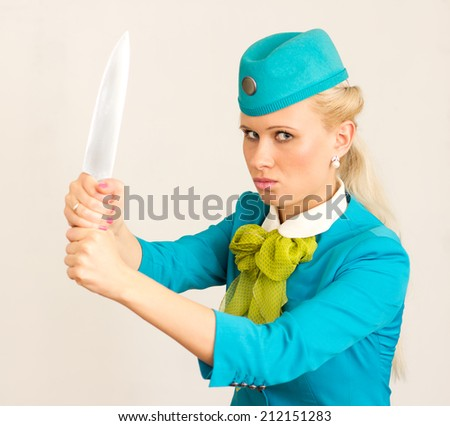 Angry stewardess holds a huge knife in hand. - stock photo