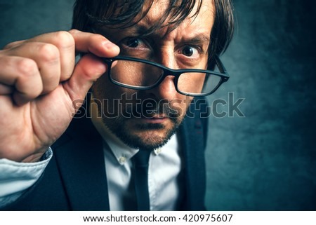 Angry tax inspector looking serious and determined, adult businessperson with glasses - stock photo