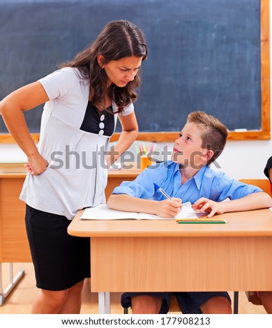 Angry teacher looking at pupil's homework - stock photo