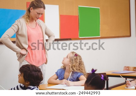 Angry teacher looking pupil with hands on hips at the elementary school - stock photo