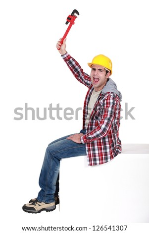 Angry tradesman holding a pipe wrench - stock photo