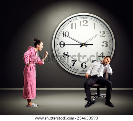 angry wife screaming at lazy husband. photo in dark room with big clock on the wall - stock photo