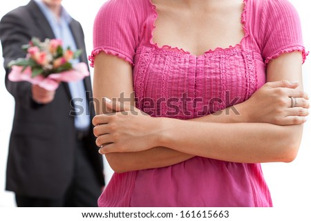 Angry woman and a man with bouquet of flowers in the background - stock photo