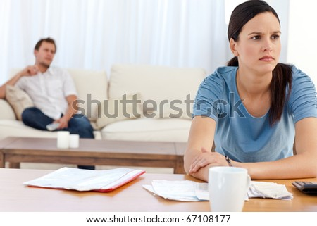 Angry woman doing her account while her boyfriend relaxing on the sofa - stock photo
