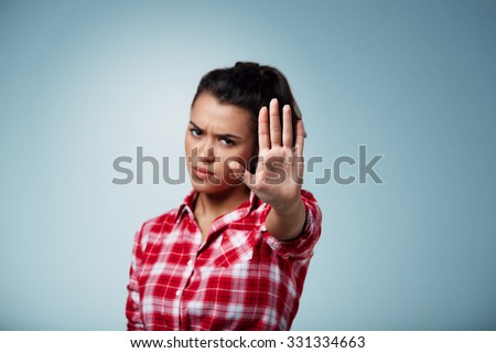 Angry woman gesturing stop sign over isolated background. Focus on hand  - stock photo