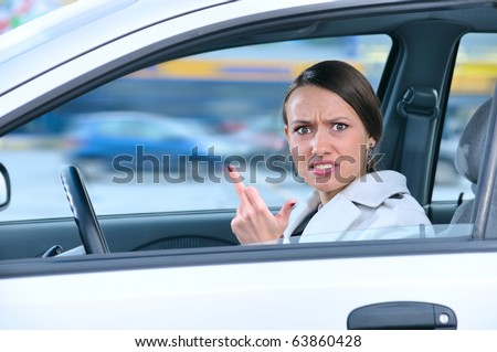 angry woman in a car is showing her middle finger - stock photo
