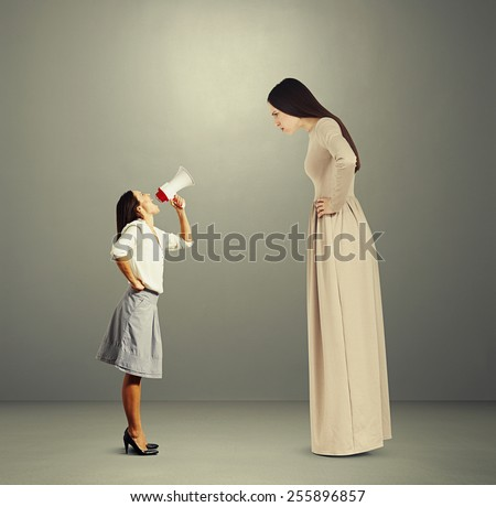 angry woman in long dress staring at small screaming woman with megaphone. photo over dark background - stock photo