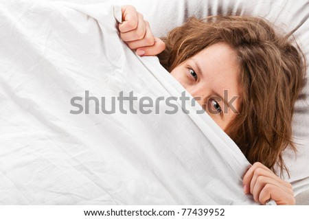 angry woman is lying in bed under blanket and does not want to wake up - stock photo