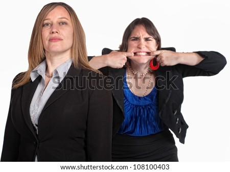 Angry woman makes face behind person over white - stock photo