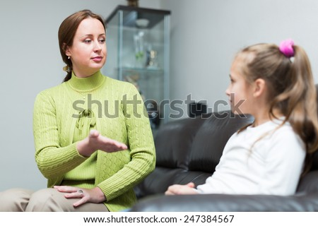 Angry woman scolding sad little daughter at home interior   - stock photo