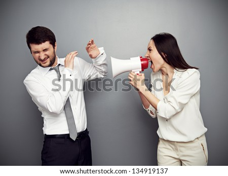 angry woman shouting at the man over dark background - stock photo