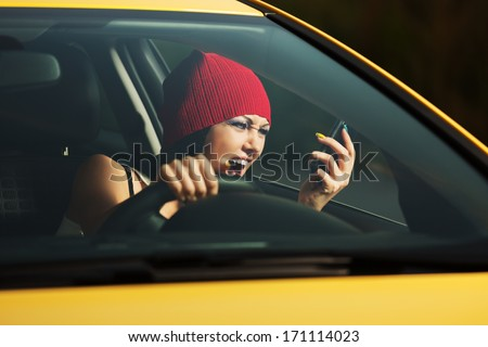 Angry woman shouting on the cell phone in a car - stock photo