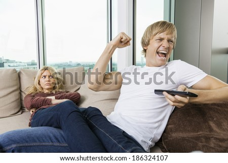 Angry woman staring at cheerful man as he watches TV in living room at home - stock photo