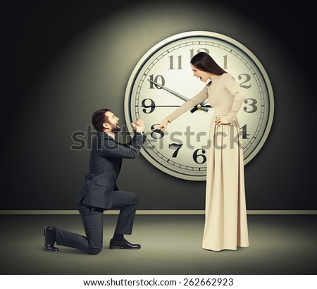 angry yelling woman pointing finger at crying man in dark room with big clock on the wall - stock photo