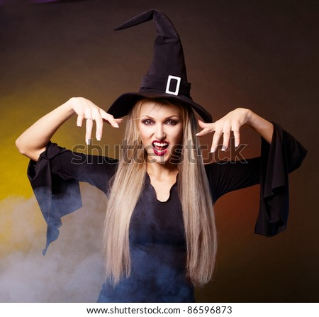 angry young blond witch with  clouds of blue smoke around her,against black and yellow background - stock photo