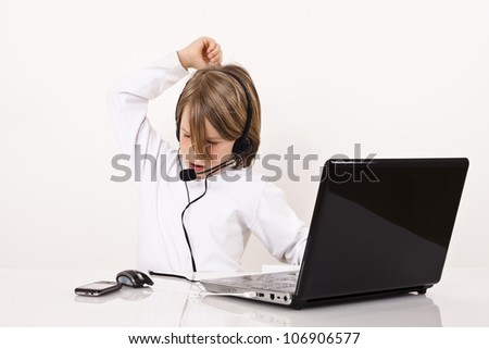 Angry young boy with a headset looks something on the Internet. - stock photo