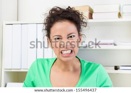 Angry young business woman in office - stock photo