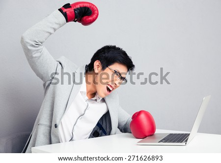 Angry young businessman sitting at the table in boxing gloves. Ready to hit the laptop - stock photo