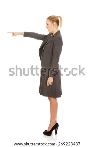 Angry young businesswoman pointing aside. - stock photo