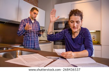 Angry young couple arguing by their many debts at home. Financial family problems concept. - stock photo