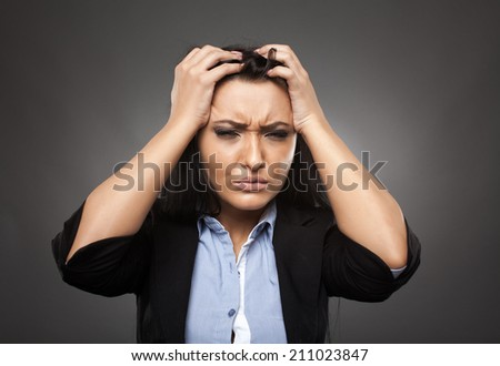 Angry young hispanic businesswoman, studio portrait on gray - stock photo