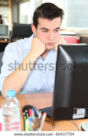 Angry young man at work - stock photo