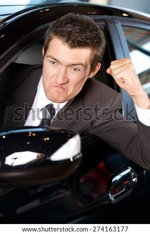 Angry young man clenching his fist, sitting in new car - stock photo