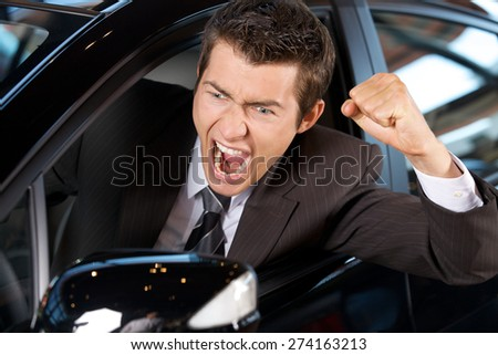 Angry young man clenching his fist, sitting in new car and shouting - stock photo