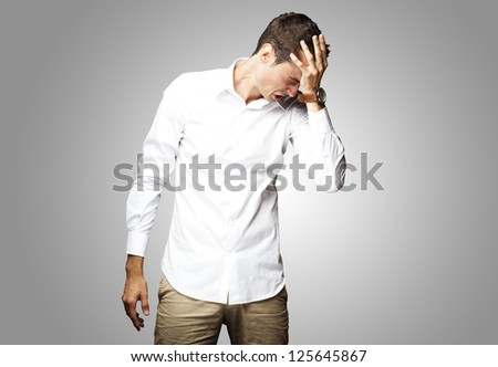 Angry young man doing frustration gesture over grey background - stock photo