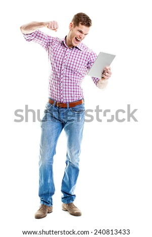 Angry young man punching his tablet pc with his fist  - stock photo