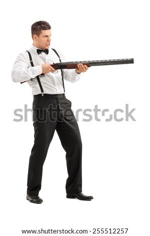 Angry young man shooting at something with a shotgun isolated on white background  - stock photo
